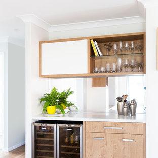 Aménagement d'un bar de salon linéaire scandinave de taille moyenne avec un placard à porte plane, des portes de placard en bois clair, un plan de travail en surface solide, une crédence en carreau de miroir et un sol en vinyl.