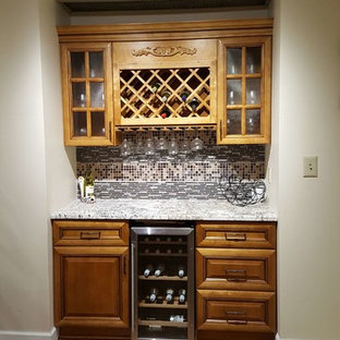 Inspiration for a small classic single-wall wet bar in Orlando with no sink, raised-panel cabinets, medium wood cabinets, granite worktops, multi-coloured splashback, mosaic tiled splashback, medium hardwood flooring and brown floors.