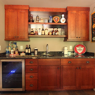 Home bar with quarter sawn oak stained cabinets and black granite countertops