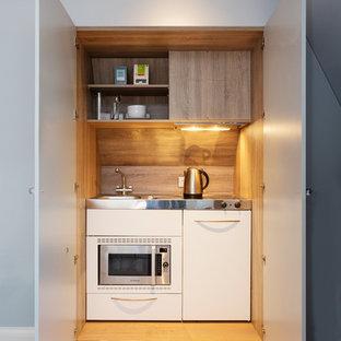 Immagine di un piccolo angolo bar con lavandino contemporaneo con lavello integrato, nessun'anta, top in acciaio inossidabile e pavimento beige
