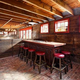 ボストンの中サイズのカントリー風おしゃれな着席型バー (ll型、家具調キャビネット、濃色木目調キャビネット、木材カウンター、レンガの床、赤い床) の写真