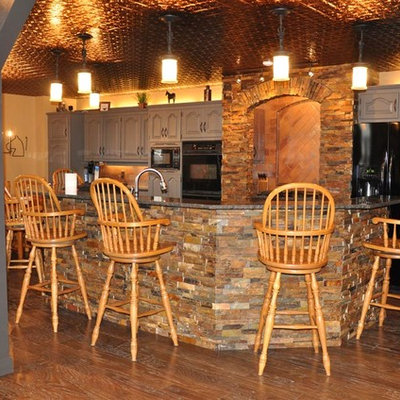 Mid-sized mountain style u-shaped medium tone wood floor and brown floor wet bar photo in Other with raised-panel cabinets, gray cabinets, granite countertops and beige backsplash