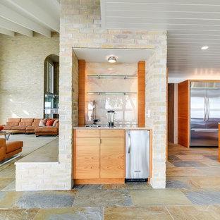 オースティンの小さいミッドセンチュリースタイルのおしゃれなウェット バー (I型、アンダーカウンターシンク、フラットパネル扉のキャビネット、中間色木目調キャビネット、ガラス板のキッチンパネル、マルチカラーの床、白いキッチンカウンター、スレートの床) の写真