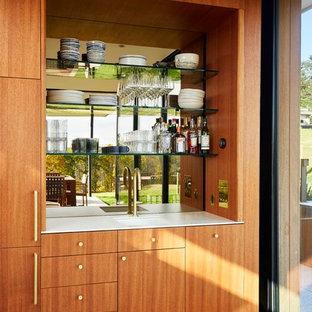Idee per un armadio bar moderno con lavello sottopiano, ante lisce, ante in legno scuro, paraspruzzi a specchio, pavimento in legno massello medio e top bianco