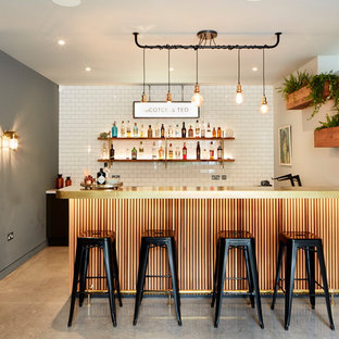 Inspiration for a large contemporary galley home bar in London with flat-panel cabinets, white cabinets, marble worktops, concrete flooring and grey floors.