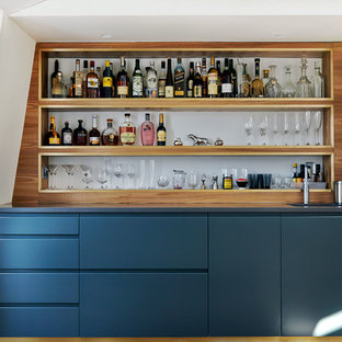 Inspiration for a large contemporary single-wall wet bar in London with flat-panel cabinets and blue cabinets.