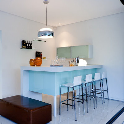 Example of a small trendy l-shaped white floor seated home bar design in Other with white countertops