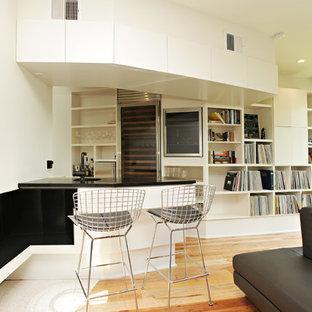 Exemple d'un petit bar de salon parallèle tendance avec des tabourets, un placard sans porte, des portes de placard blanches, un sol en bois brun, un évier encastré et un plan de travail en granite.