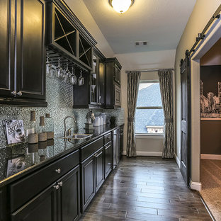 Wet bar - large traditional single-wall dark wood floor and brown floor wet bar idea in Houston with a drop-in sink, raised-panel cabinets, black cabinets, gray backsplash, metal backsplash and granite countertops