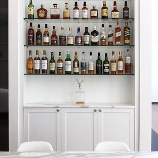 Traditional home bar in New York with white cabinets, marble worktops, white splashback, metro tiled splashback and shaker cabinets.