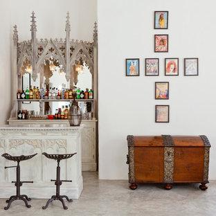 Ejemplo de bar en casa con barra de bar de galera, ecléctico, de tamaño medio, sin pila, con puertas de armario blancas, salpicadero con efecto espejo, armarios abiertos, encimera de mármol y suelo de cemento