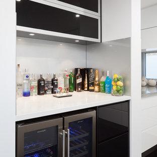 Idee per un angolo bar minimalista con ante lisce, ante nere, top in quarzo composito, paraspruzzi grigio, paraspruzzi con lastra di vetro e top bianco