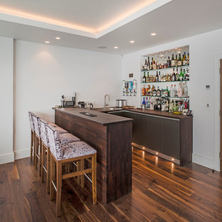 Photo of a contemporary u-shaped breakfast bar in London with flat-panel cabinets, wood worktops, medium hardwood flooring and brown worktops.