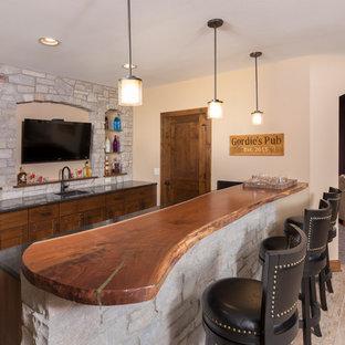 ミルウォーキーの広いラスティックスタイルのおしゃれな着席型バー (ll型、アンダーカウンターシンク、中間色木目調キャビネット、木材カウンター、グレーのキッチンパネル、石タイルのキッチンパネル、セラミックタイルの床、茶色いキッチンカウンター、シェーカースタイル扉のキャビネット、ベージュの床) の写真