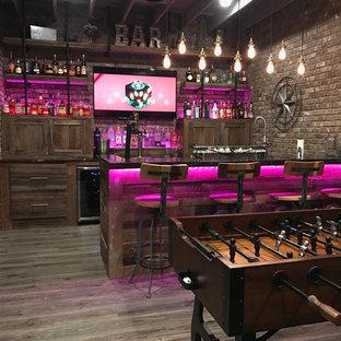 Immagine di un bancone bar industriale con ante con riquadro incassato, ante con finitura invecchiata, paraspruzzi marrone, paraspruzzi in mattoni, pavimento in legno massello medio e pavimento grigio