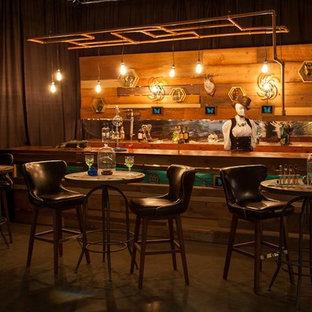 ポートランドの広いインダストリアルスタイルのおしゃれなホームバー (ll型、シンクなし、フラットパネル扉のキャビネット、ヴィンテージ仕上げキャビネット、銅製カウンター、コンクリートの床) の写真