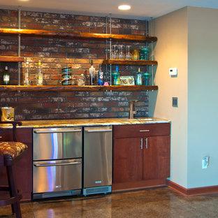 Idee per un armadio bar design con lavello sottopiano, ante lisce, ante in legno bruno, top in granito, paraspruzzi rosso, paraspruzzi in mattoni, pavimento in cemento e pavimento marrone