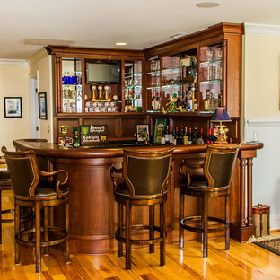 Seated home bar - mid-sized traditional u-shaped medium tone wood floor seated home bar idea in Richmond with recessed-panel cabinets, dark wood cabinets, wood countertops and brown countertops