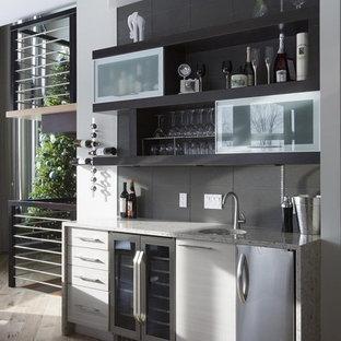 Immagine di un piccolo angolo bar con lavandino design con lavello sottopiano, ante lisce, ante grigie, top in quarzo composito, paraspruzzi grigio, parquet chiaro e pavimento grigio
