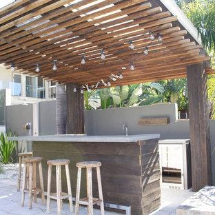 Immagine di un piccolo bancone bar costiero con lavello sottopiano, ante in legno bruno, top in cemento e paraspruzzi grigio