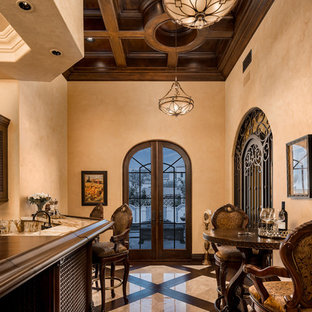 Huge tuscan l-shaped porcelain floor and multicolored floor seated home bar photo in Phoenix with a drop-in sink, glass-front cabinets, dark wood cabinets, marble countertops, multicolored backsplash and marble backsplash