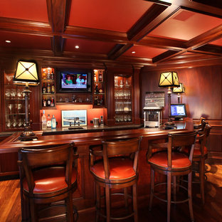 Example of a mid-sized classic u-shaped dark wood floor seated home bar design in Philadelphia with recessed-panel cabinets, dark wood cabinets, wood countertops and brown countertops
