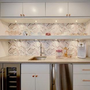 オースティンのトランジショナルスタイルのおしゃれなウェット バー (I型、アンダーカウンターシンク、フラットパネル扉のキャビネット、白いキャビネット、ピンクのキッチンパネル、グレーのキッチンカウンター) の写真