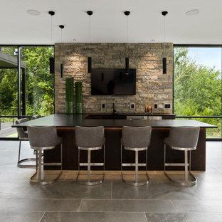 カンザスシティのコンテンポラリースタイルのおしゃれな着席型バー (コの字型、石タイルのキッチンパネル、グレーの床、黒いキッチンカウンター) の写真