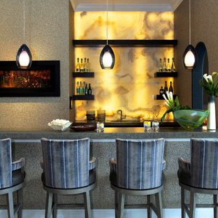 Immagine di un bancone bar contemporaneo con paraspruzzi giallo, paraspruzzi in lastra di pietra, ante nere, top in granito, pavimento in pietra calcarea, pavimento beige e top grigio