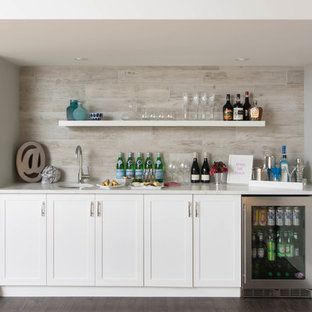 Traditional single-wall wet bar in Toronto with a submerged sink, shaker cabinets, white cabinets, grey splashback and dark hardwood flooring.