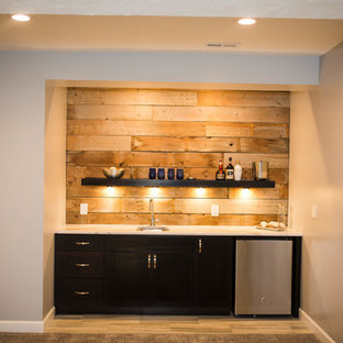 Inspiration for a medium sized rustic single-wall wet bar in Omaha with a submerged sink, flat-panel cabinets, black cabinets, marble worktops, brown splashback, wood splashback and light hardwood flooring.