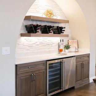 Immagine di un angolo bar tradizionale con ante con bugna sagomata, ante in legno scuro, paraspruzzi bianco, pavimento in legno massello medio, pavimento marrone e top bianco