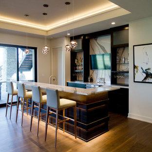 カンザスシティの広いコンテンポラリースタイルのおしゃれな着席型バー (L型、アンダーカウンターシンク、御影石カウンター、マルチカラーのキッチンパネル、石スラブのキッチンパネル、無垢フローリング、茶色い床、マルチカラーのキッチンカウンター) の写真