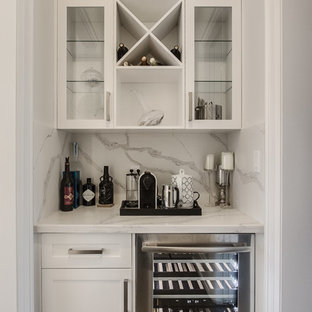 Small contemporary single-wall wet bar in Toronto with no sink, shaker cabinets, white cabinets, marble worktops, white splashback, marble splashback, dark hardwood flooring, brown floors and white worktops.