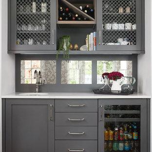 Foto di un angolo bar con lavandino chic con lavello sottopiano, ante grigie, paraspruzzi a specchio, parquet scuro, pavimento marrone e top bianco