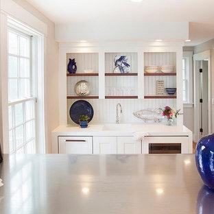 Inspiration pour un petit bar de salon avec évier linéaire marin avec un évier intégré, un placard à porte shaker, des portes de placard blanches, un plan de travail en surface solide, une crédence blanche, une crédence en bois et un sol en bois clair.