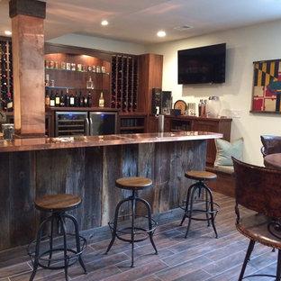 Immagine di un grande bancone bar industriale con lavello sottopiano, ante con riquadro incassato, ante in legno scuro, top in rame e pavimento in gres porcellanato