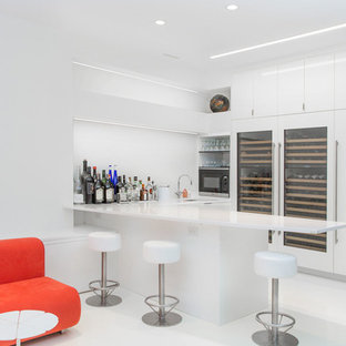 Mid-sized minimalist l-shaped white floor wet bar photo in New York with flat-panel cabinets, white cabinets, quartz countertops and white backsplash