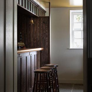ロンドンの小さいおしゃれなウェット バー (I型、シェーカースタイル扉のキャビネット、濃色木目調キャビネット、木材カウンター、茶色いキッチンパネル、塗装板のキッチンパネル、ライムストーンの床、ベージュのキッチンカウンター) の写真