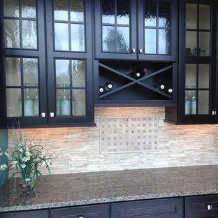 Esempio di un piccolo angolo bar con lavandino chic con ante di vetro, ante nere, top in granito, paraspruzzi beige e paraspruzzi con piastrelle in pietra