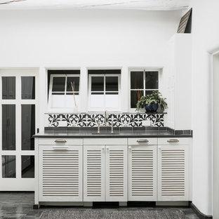 サンタフェスタイルのおしゃれなウェット バー (I型、ルーバー扉のキャビネット、白いキャビネット、マルチカラーのキッチンパネル、黒い床、黒いキッチンカウンター) の写真