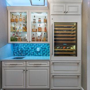 Klassisk inredning av en liten vita vitt hemmabar med vask, med en undermonterad diskho, luckor med upphöjd panel, vita skåp, bänkskiva i kvarts, blått stänkskydd, stänkskydd i glaskakel, mellanmörkt trägolv och brunt golv