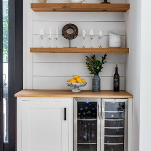 This is an example of a small transitional single-wall home bar in Boston with no sink, shaker cabinets, white cabinets, wood benchtops, white splashback, timber splashback, light hardwood floors, beige floor and beige benchtop.