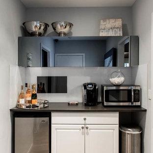 ニューヨークの小さいモダンスタイルのおしゃれなホームバー (I型、落し込みパネル扉のキャビネット、白いキャビネット、人工大理石カウンター、淡色無垢フローリング) の写真