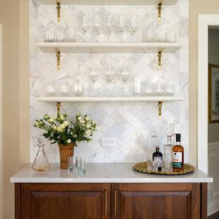 ニューヨークの広いトラディショナルスタイルのおしゃれなホームバー (シンクなし、中間色木目調キャビネット、クオーツストーンカウンター、白いキッチンパネル、サブウェイタイルのキッチンパネル、セラミックタイルの床、白いキッチンカウンター、レイズドパネル扉のキャビネット) の写真