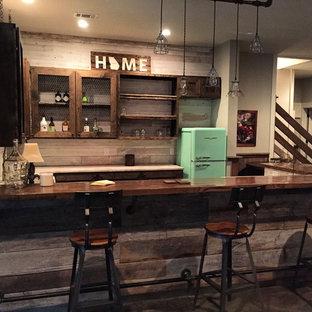 Idee per un bancone bar rustico di medie dimensioni con ante di vetro, ante in legno bruno, top in legno, paraspruzzi beige, paraspruzzi in legno e top marrone