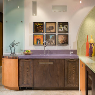 Small trendy l-shaped concrete floor wet bar photo in Kansas City with an integrated sink, flat-panel cabinets, medium tone wood cabinets, recycled glass countertops, multicolored backsplash, glass sheet backsplash and purple countertops
