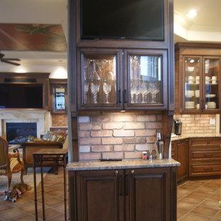 ジャクソンビルの地中海スタイルのおしゃれなホームバー (レイズドパネル扉のキャビネット、中間色木目調キャビネット、御影石カウンター、ピンクのキッチンパネル、レンガのキッチンパネル、テラコッタタイルの床) の写真
