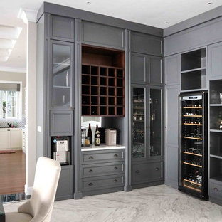 This is an example of a medium sized traditional l-shaped wet bar in Other with recessed-panel cabinets, grey cabinets, marble worktops, grey splashback, mirror splashback, marble flooring, white floors and white worktops.