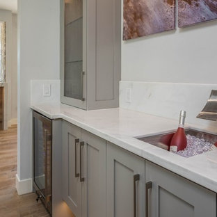 Photo of a medium sized classic single-wall wet bar in Orange County with a submerged sink, glass-front cabinets, grey cabinets, quartz worktops, light hardwood flooring and white worktops.
